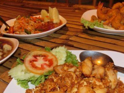 Eine leckere Mahlzeit mit Pork Garlic Pepper, Som Tam Thai und vielen anderen Leckereien.