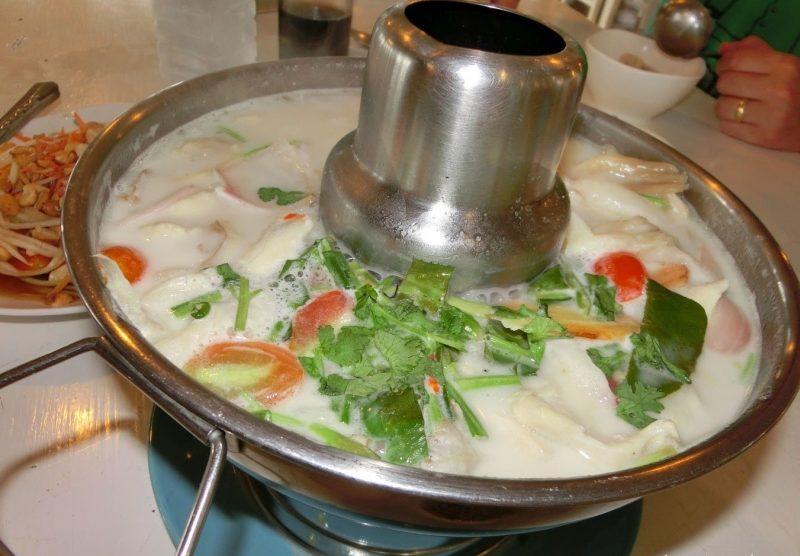 Thai Gericht Tom Kha Gai - Kokossuppe mit Huhn im beheizten Hut